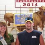 Katie Stokes received a $2.30 a pound bid from Gary Thompson of Buckeye Builders for her 592-pound best of show dairy feeder.  Also pictured is Junior Fair Queen Jessica Krulic.