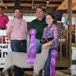 Natalie Frank's 138-pound grand champion lamb sold to Paris and Washington Insurance and Pole Barns Direct LLC, Dutchcraft Truss & Metal Inc. for $22 a pound. Pictured from left are Reggie Stoltzfus of Dutchcraft Truss & Metal Inc/Pole Barns Direct, Kelly Palmer of Paris and Washington Insurance, and Natalie Frank.