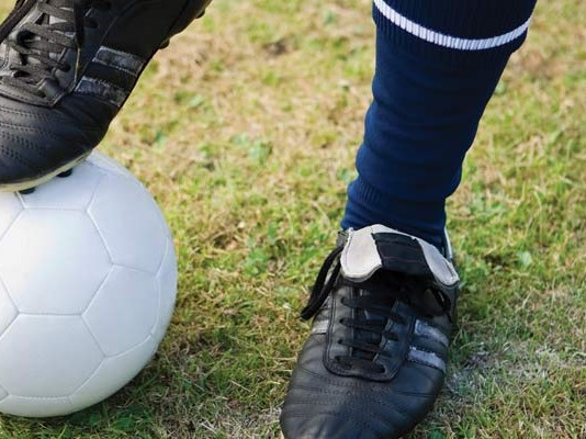 boy's foot on soccer ball
