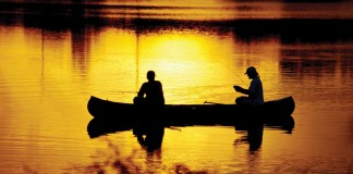 two men fishing in a canoe
