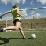 girl kicking soccer ball into goal